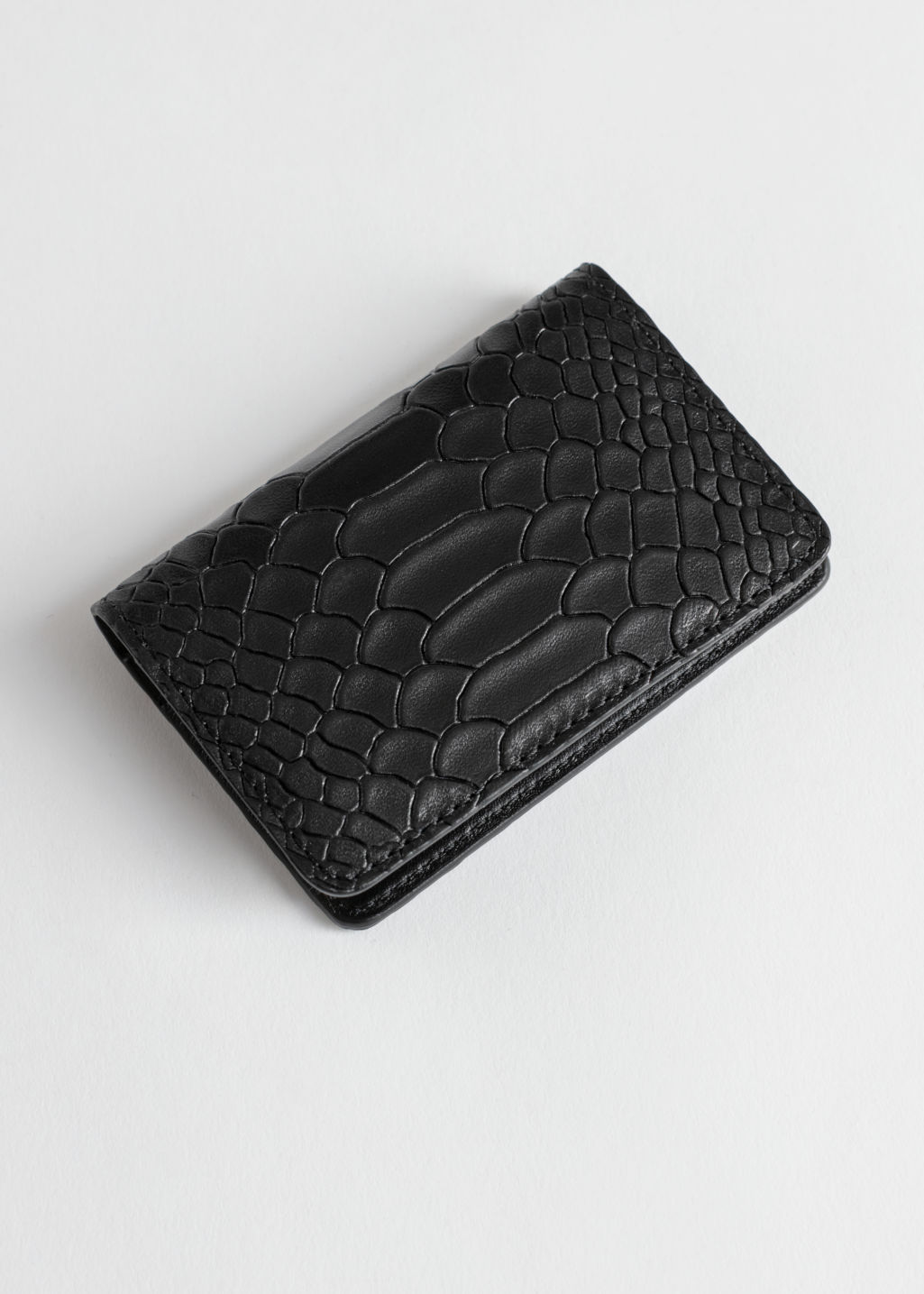 Front image of Stories snake embossed leather cardholder in black
