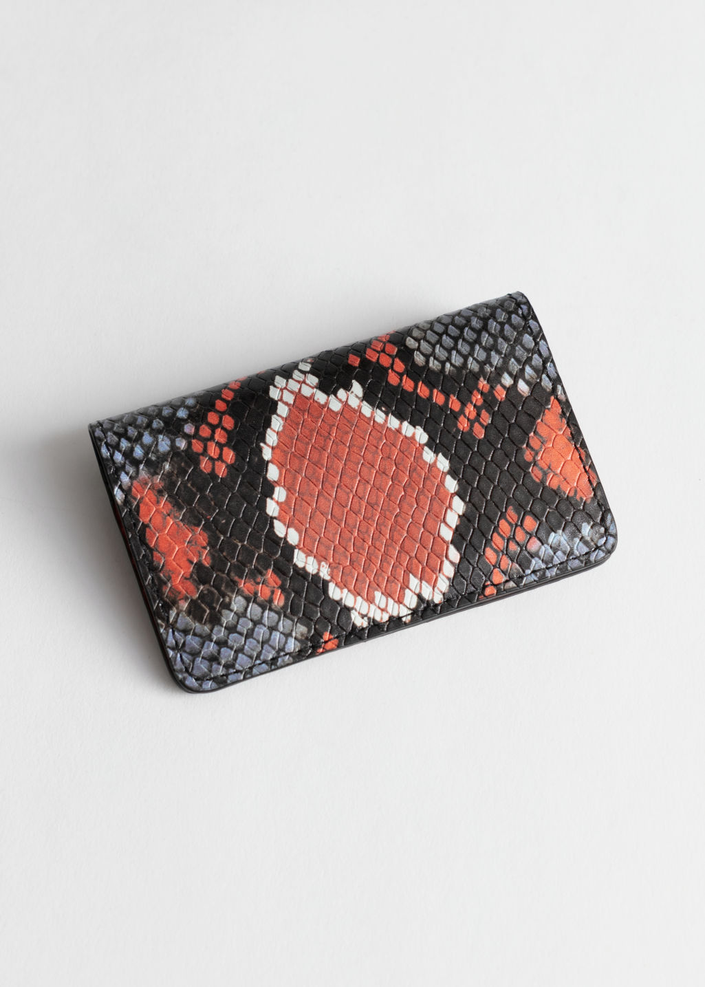 Front image of Stories snake embossed leather cardholder in orange