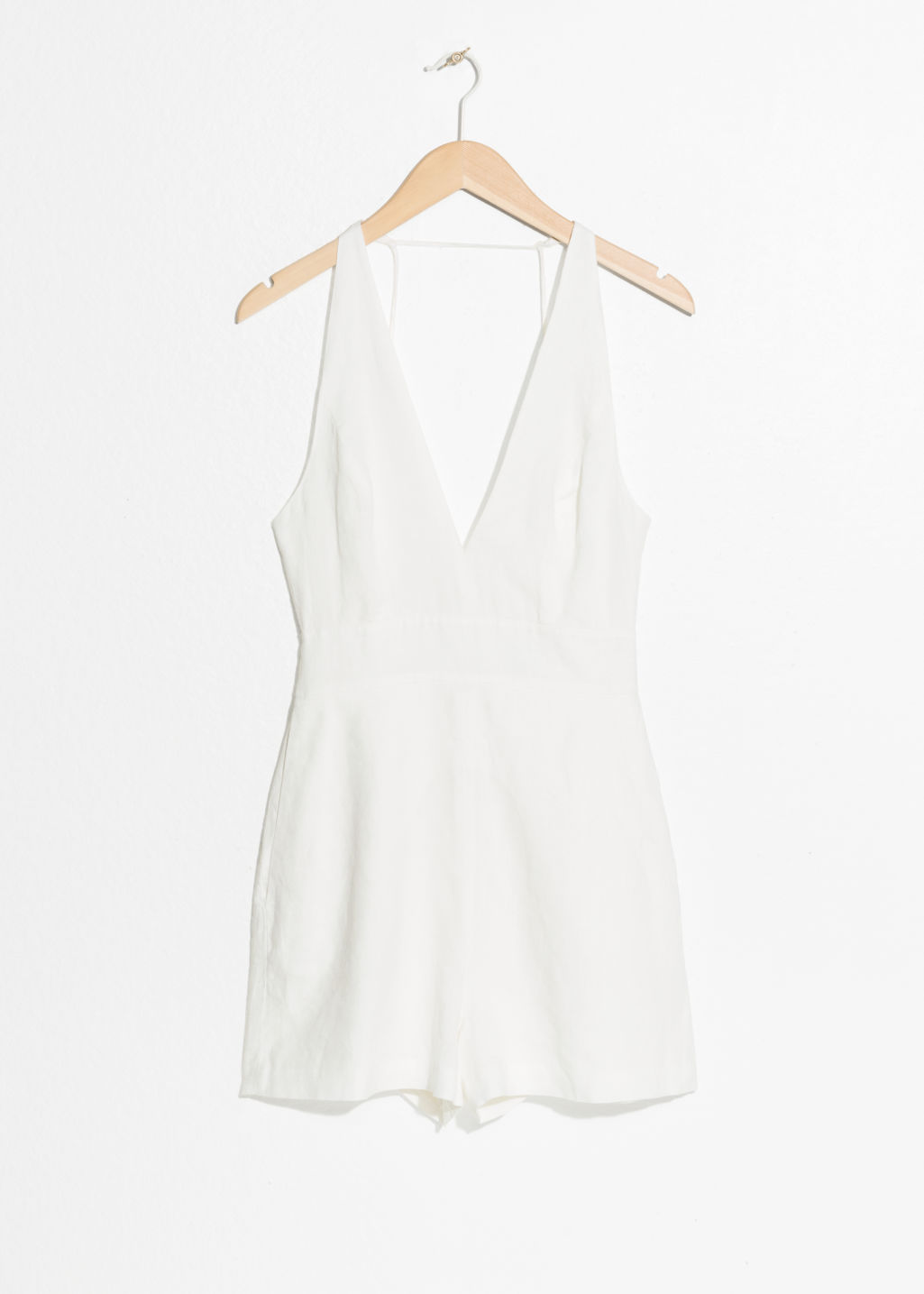 Front image of Stories plungling linen romper in white