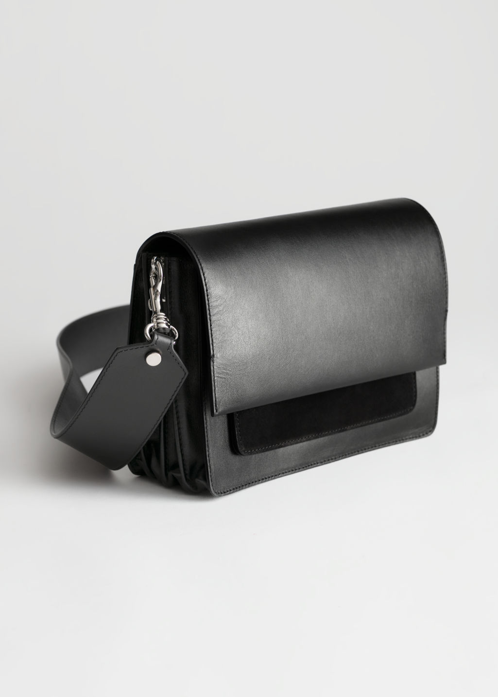Front image of Stories short leather crossbody bag in black