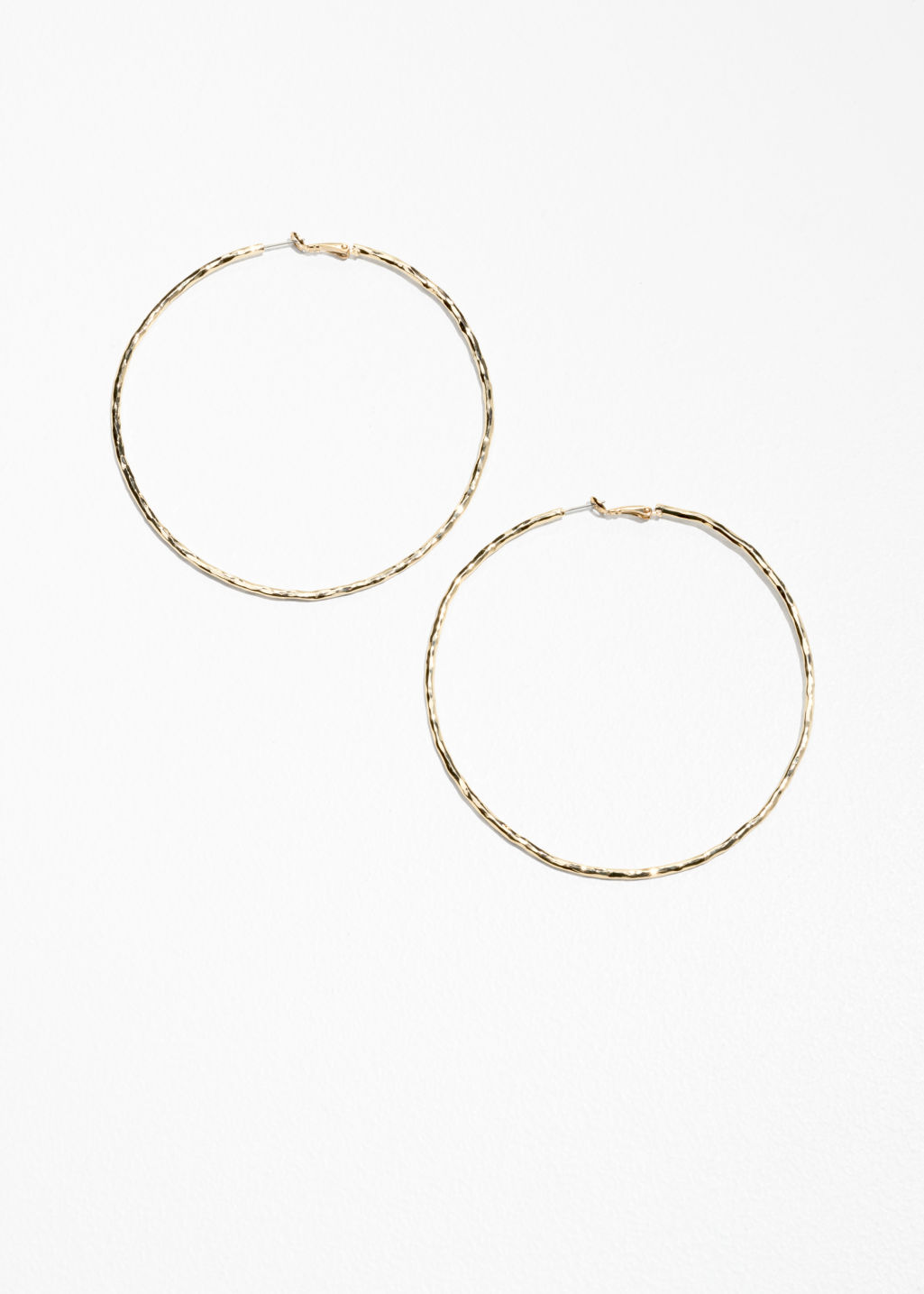 Front image of Stories hammered finish hoops in gold