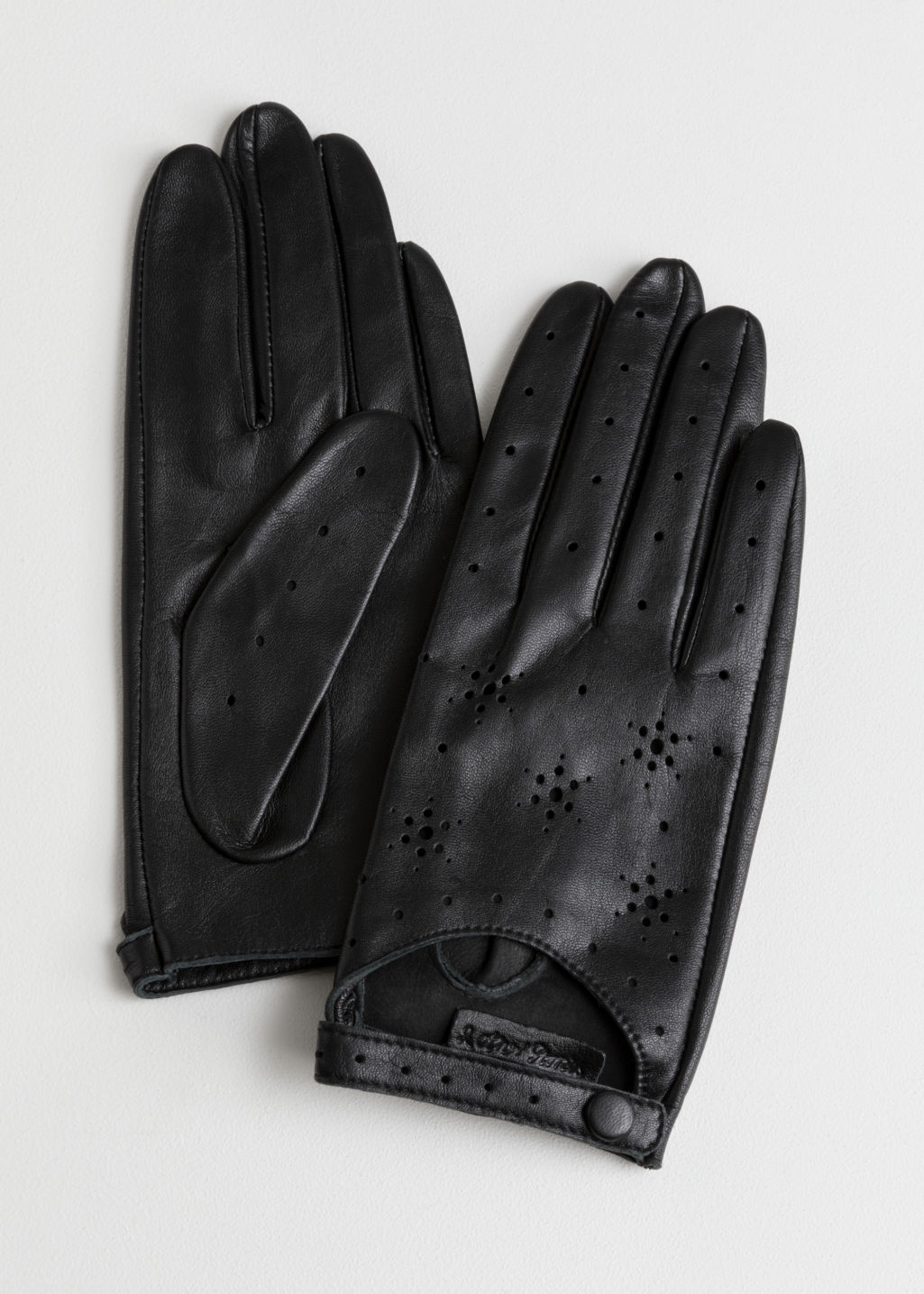 Front image of Stories star perforated leather gloves in black