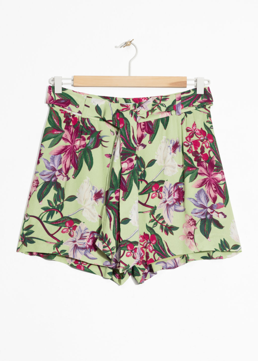 Front image of Stories tropical print shorts in green