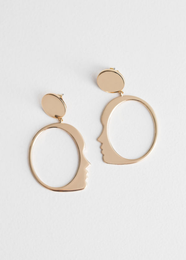Front image of Stories face dangling earrings in gold