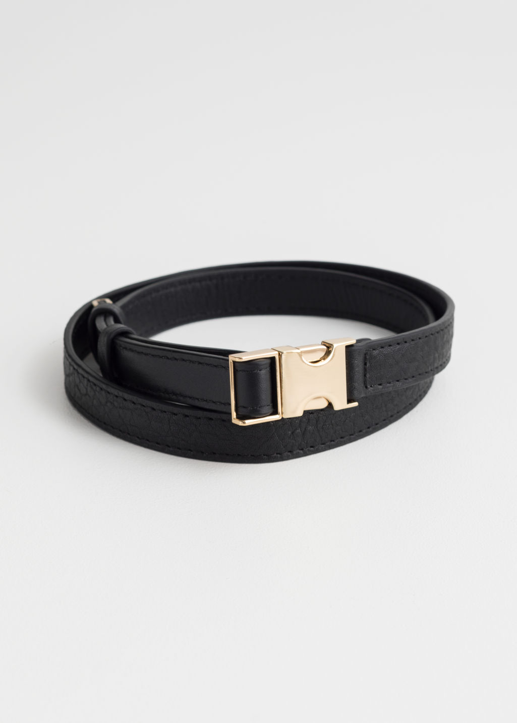 Front image of Stories metal clasp leather belt in black
