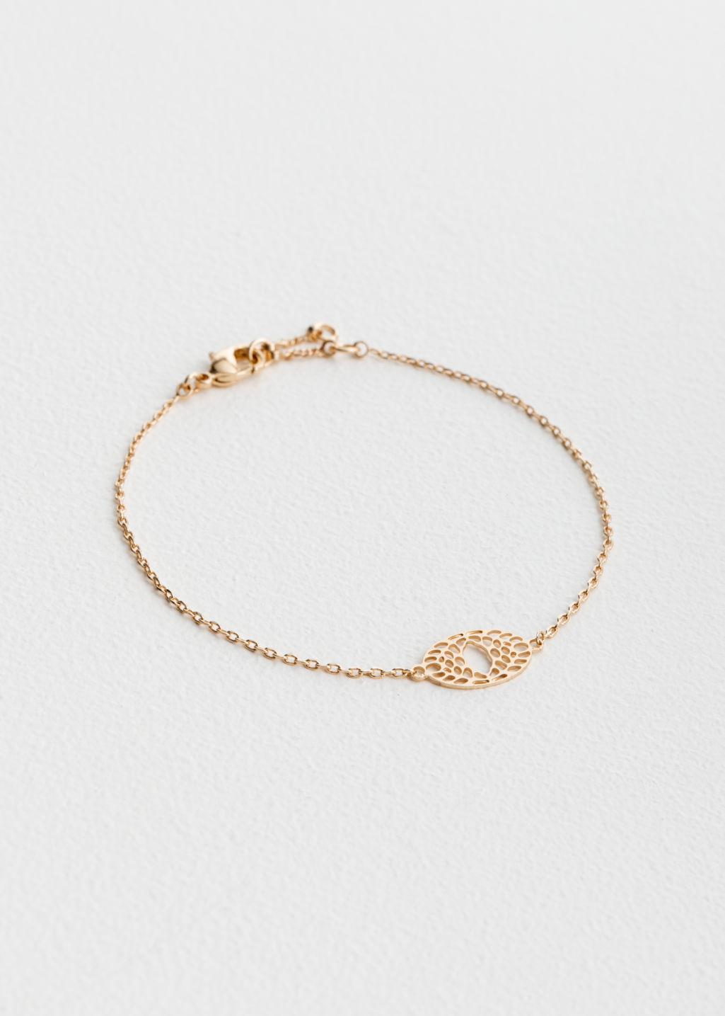 Front image of Stories cutout eye pendant bracelet in gold