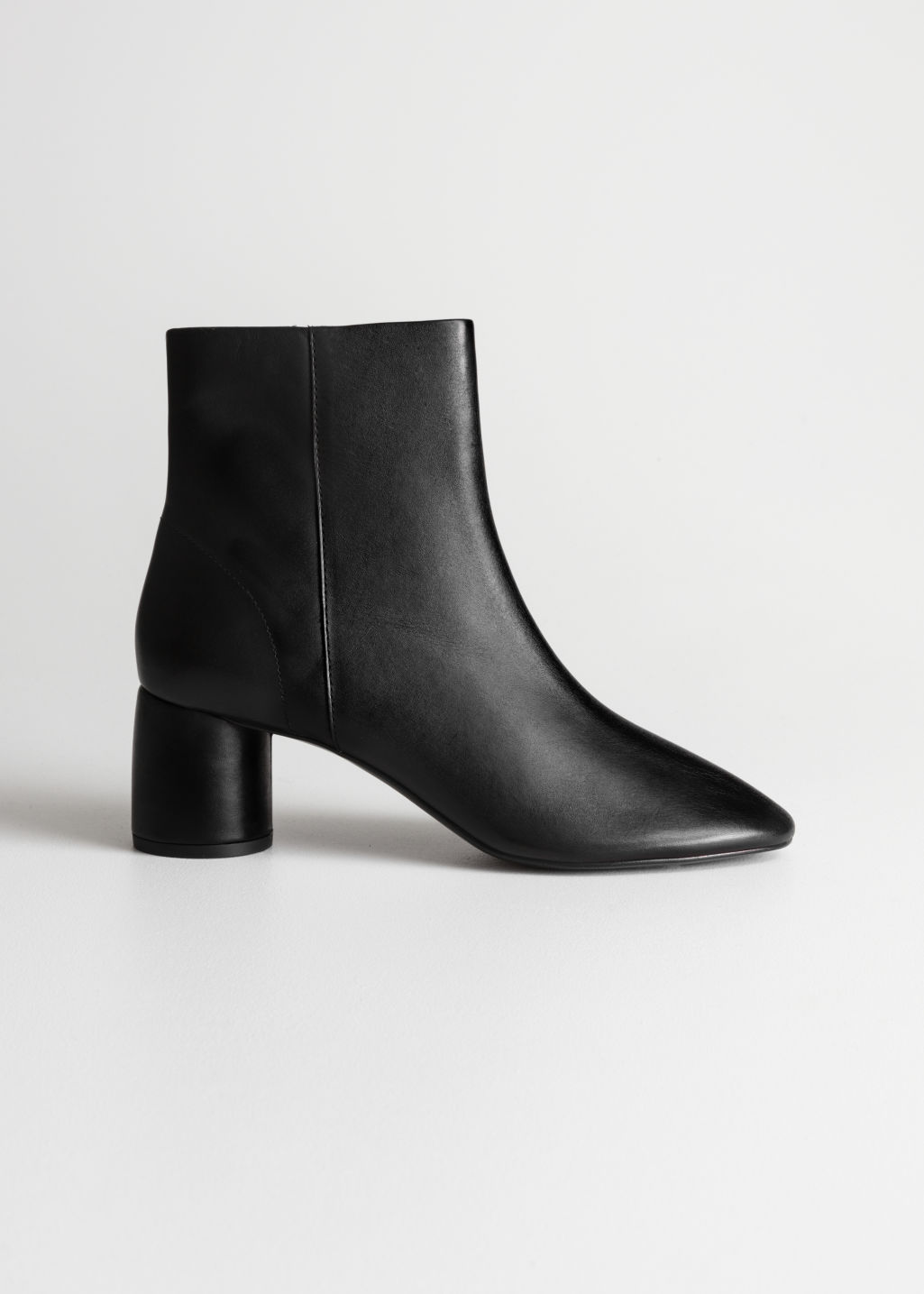 Front image of Stories cylinder heel ankle boots in black