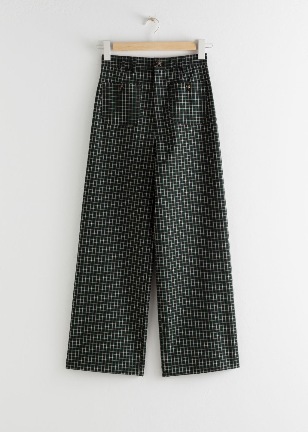 Front image of Stories kick flare plaid trousers in green