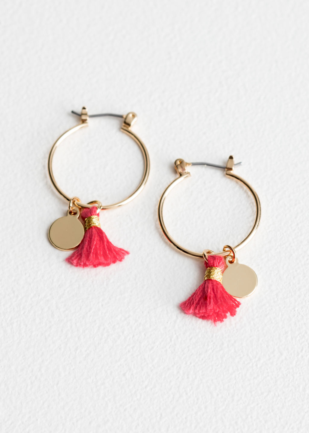 Front image of Stories tassel medallion hoop earrings in red