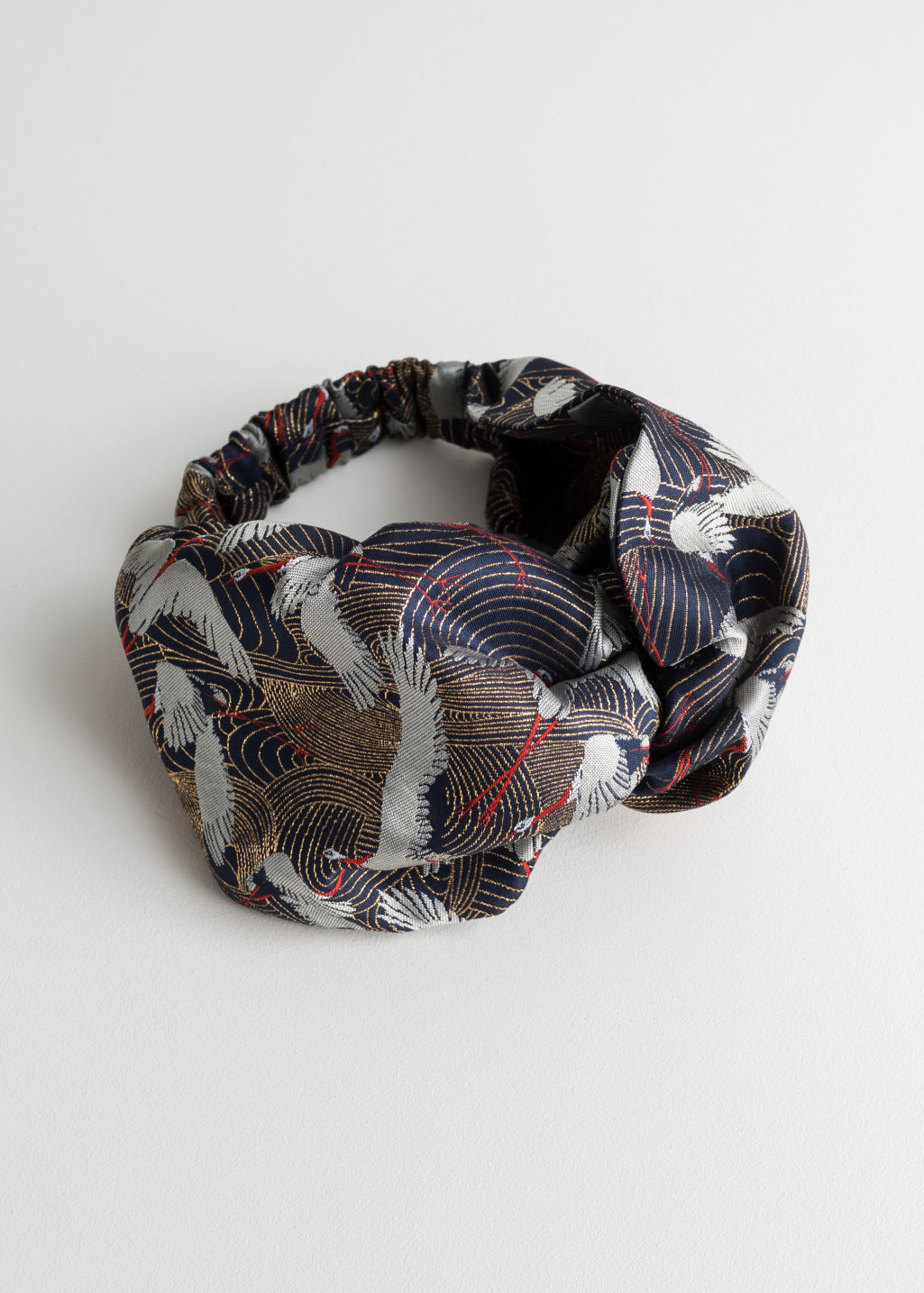 Front image of Stories crane print brocade hairband in blue