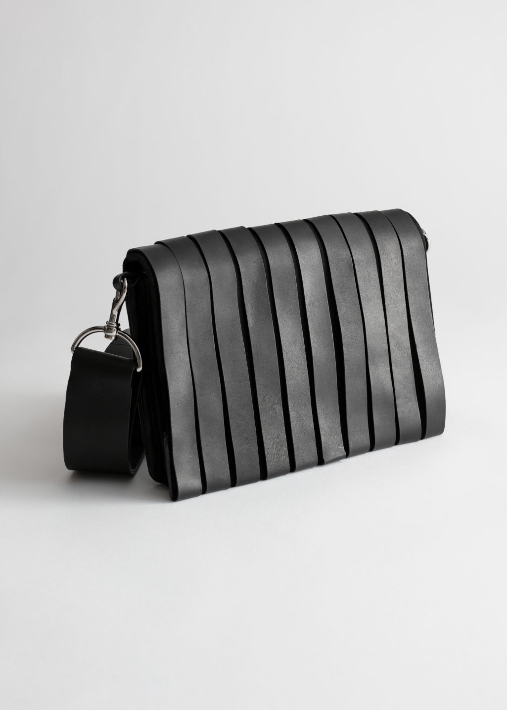 Front image of Stories leather strip crossbody bag in black