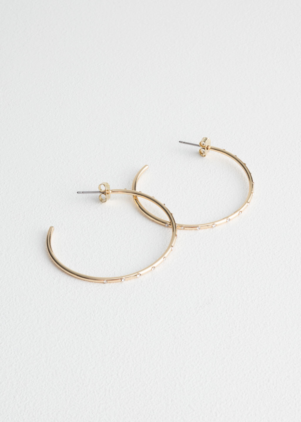 Front image of Stories crystal stone hoop earrings in gold