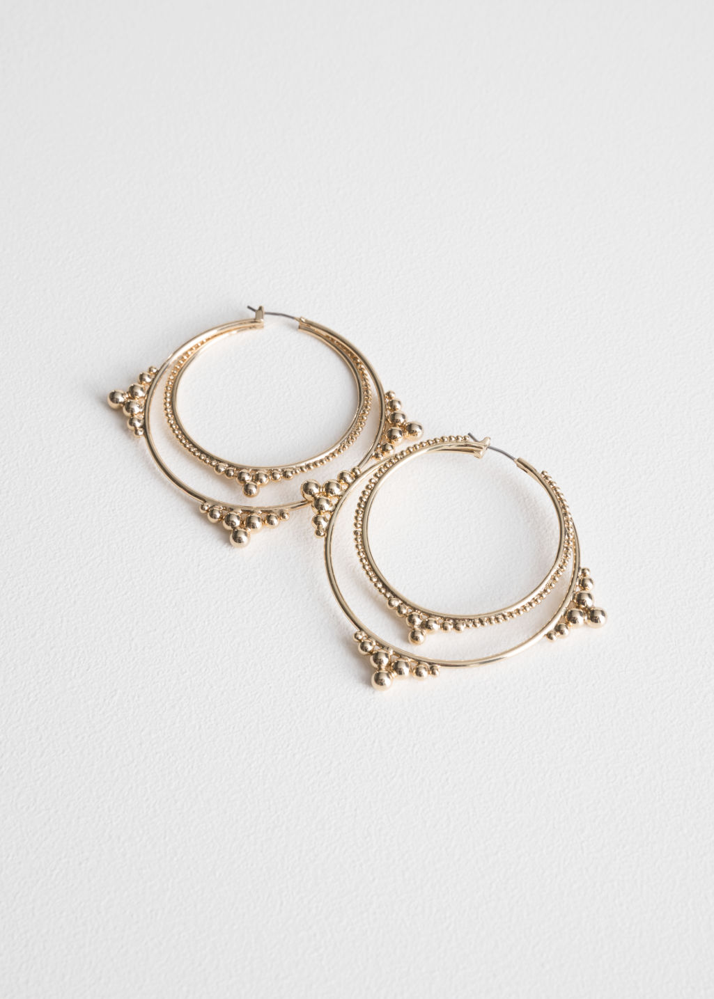 Front image of Stories ball stud hoop earrings in gold