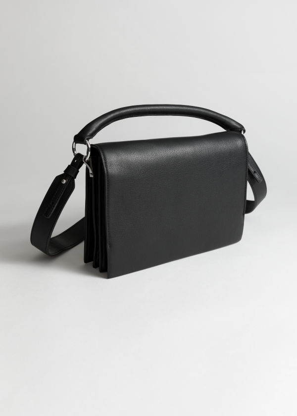 Front image of Stories leather fold over crossbody bag in black