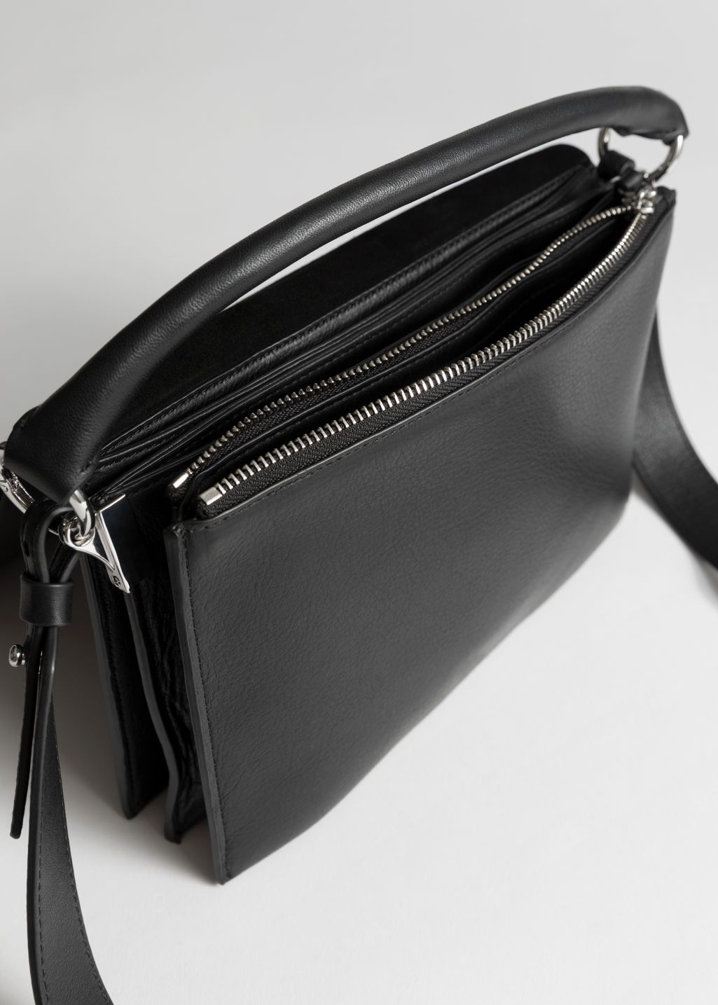 Back image of Stories leather fold over crossbody bag in black