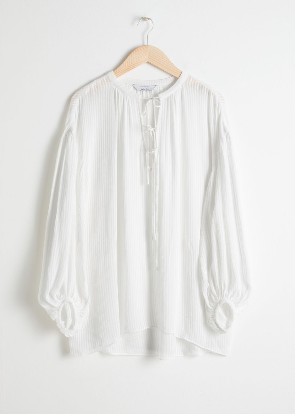 Front image of Stories sheer stripe tie blouse in white