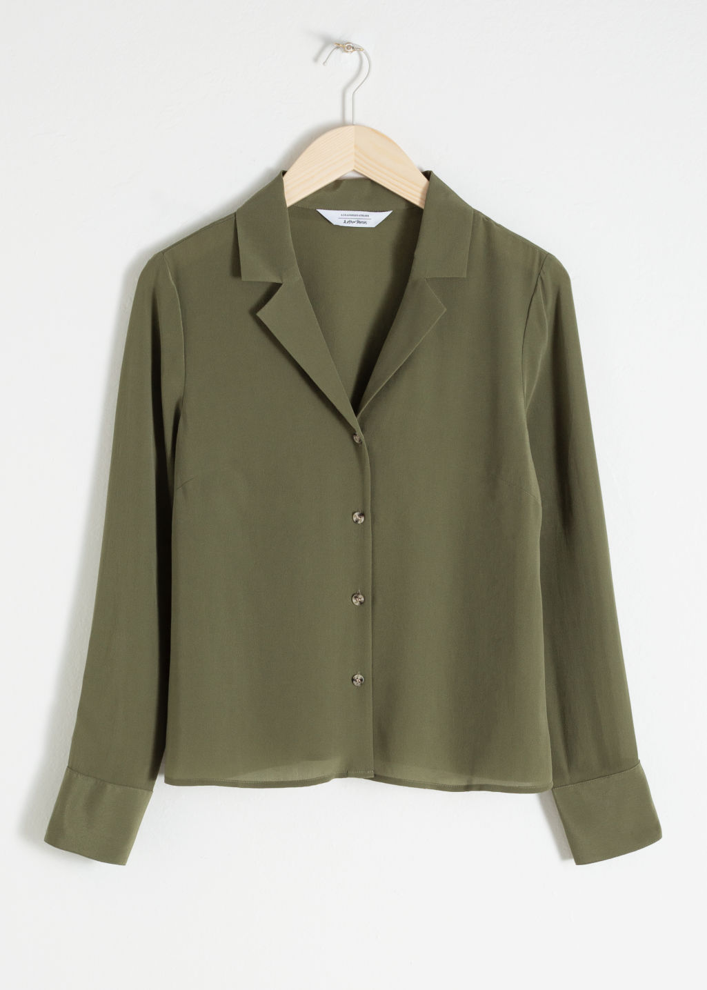Front image of Stories v-cut silk button up blouse in green