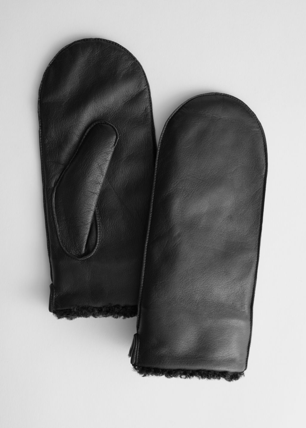 Front image of Stories leather faux shearling mittens in black
