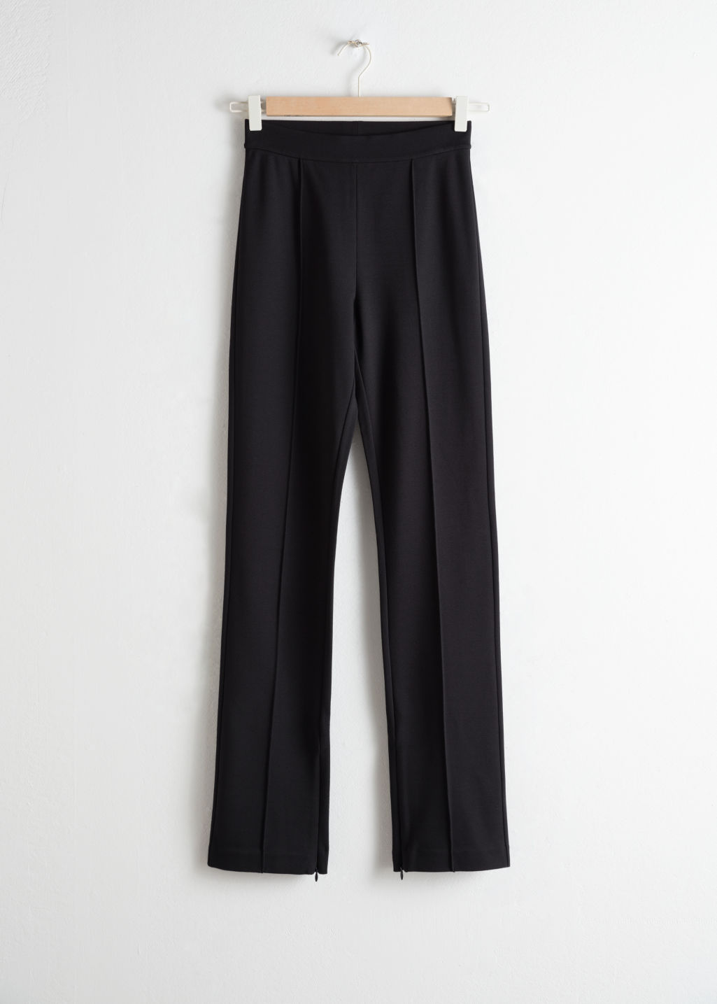 Front image of Stories stretch zipper slit trousers in black