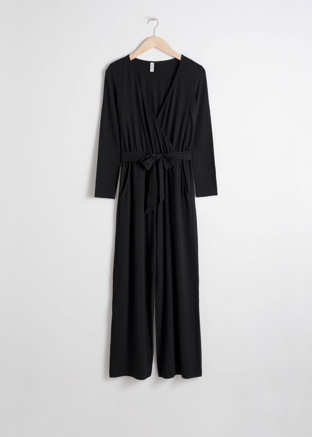 Front image of Stories belted wrap jumpsuit in black
