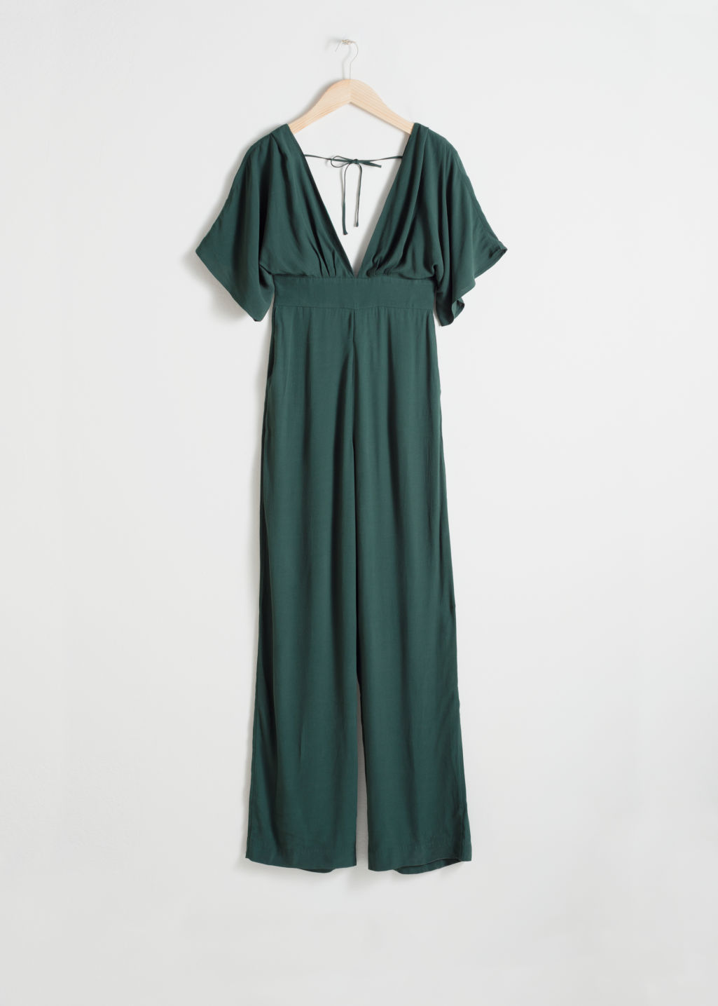 Front image of Stories plunging v-cut jumpsuit in green
