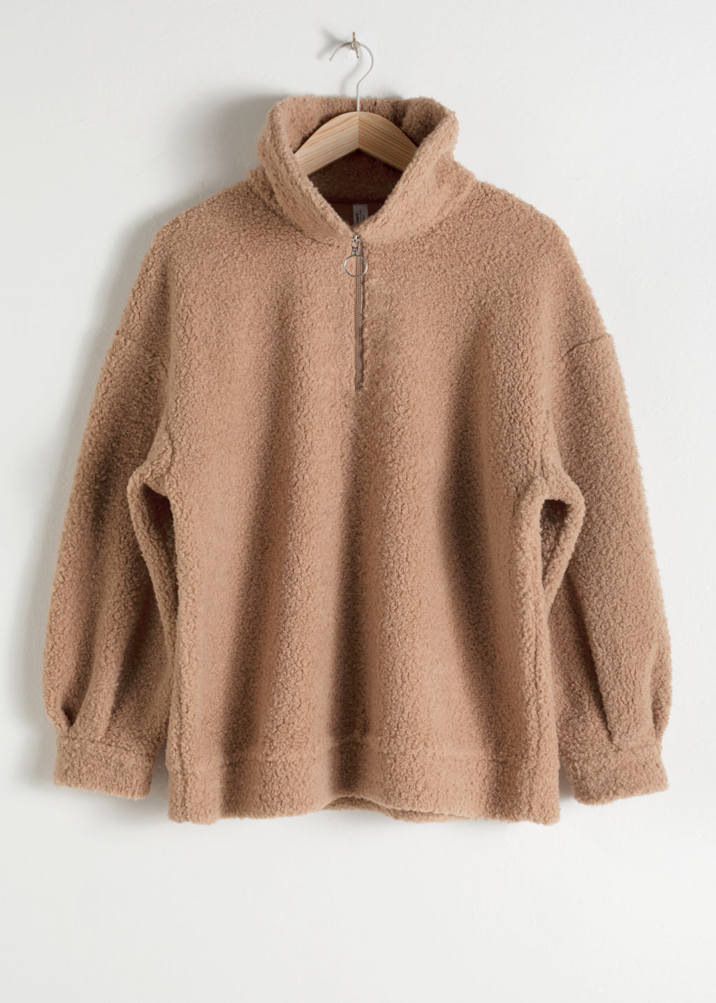 Front image of Stories faux shearling zip pullover in beige