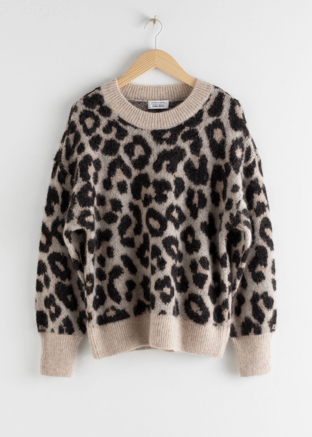 Front image of Stories oversized leopard sweater in black