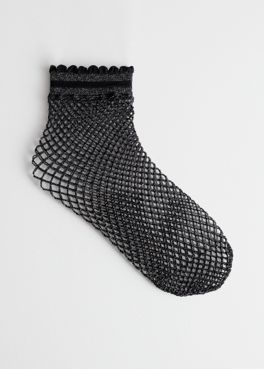 Front image of Stories glitter fishnet socks in black