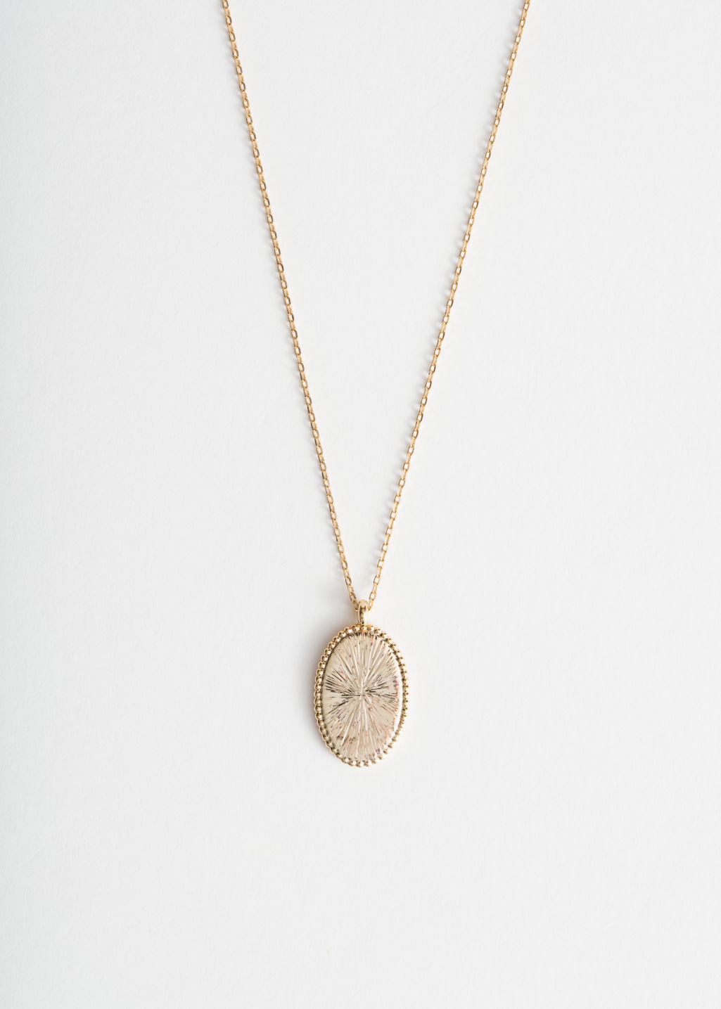Front image of Stories engraved oval pendant necklace in gold