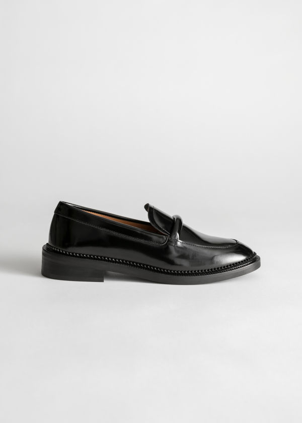 Front image of Stories leather penny loafers in black