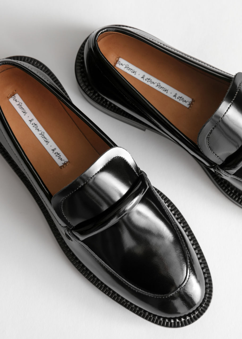 Back image of Stories leather penny loafers in black