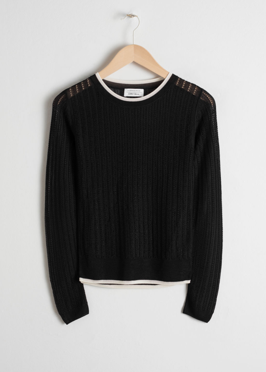 Front image of Stories sheer eyelet knit sweater in black