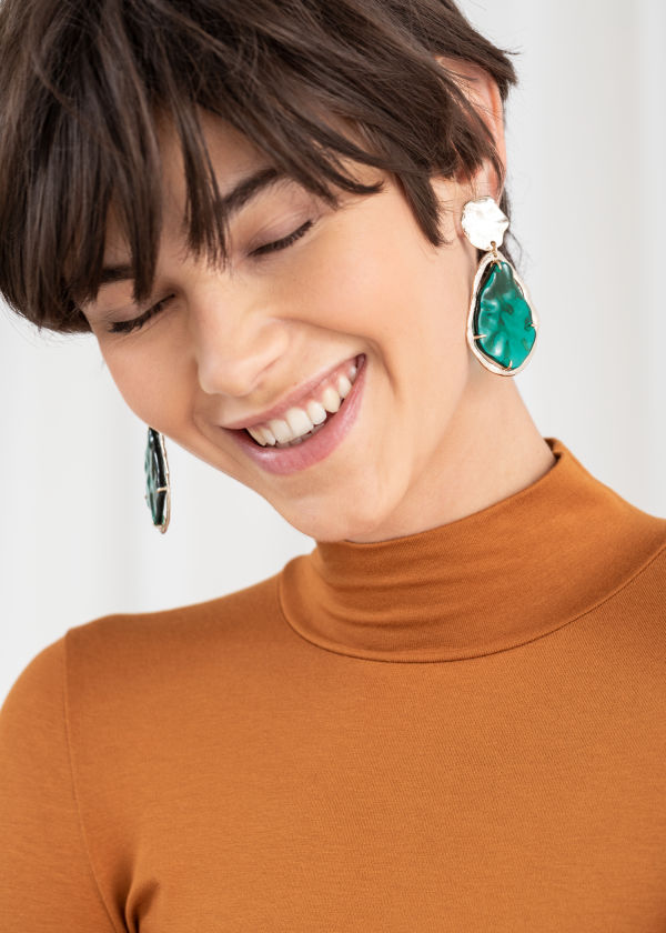 Front image of Stories gold flake hanging earrings in green