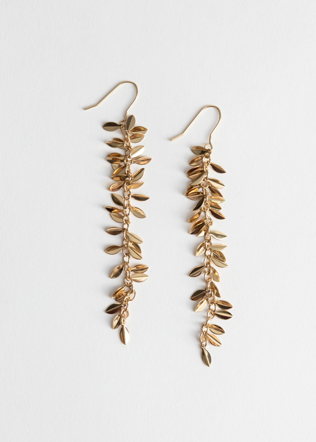Front image of Stories hanging olive branch earrings in gold