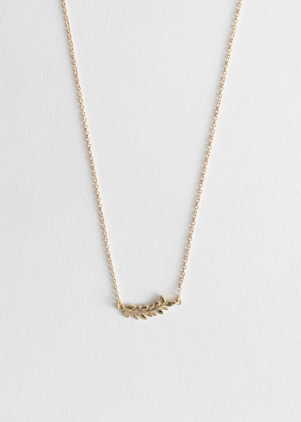 Front image of Stories olive branch charm necklace in gold