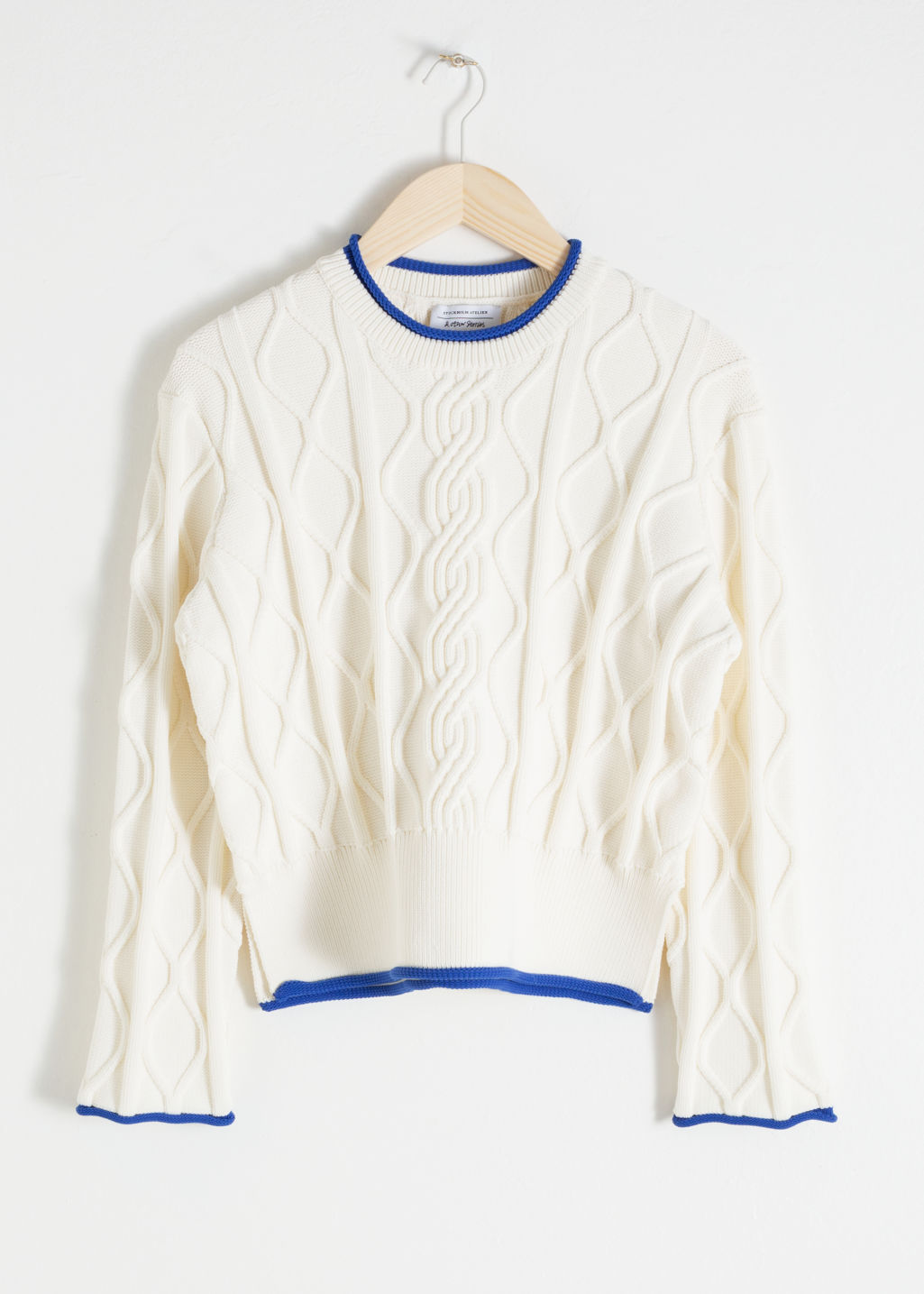 Front image of Stories structured cropped cable knit sweater in white
