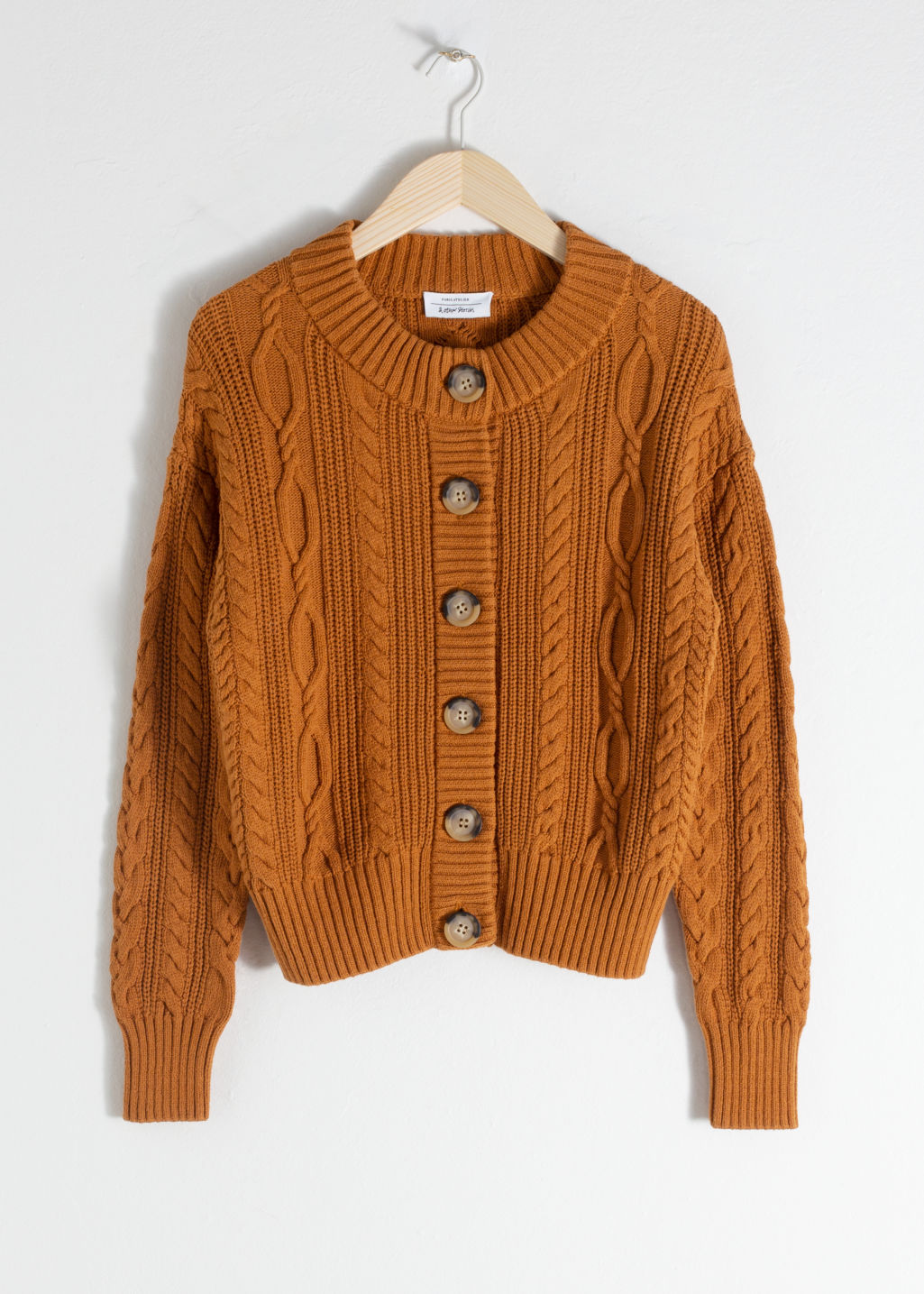 Front image of Stories cable knit cardigan in orange