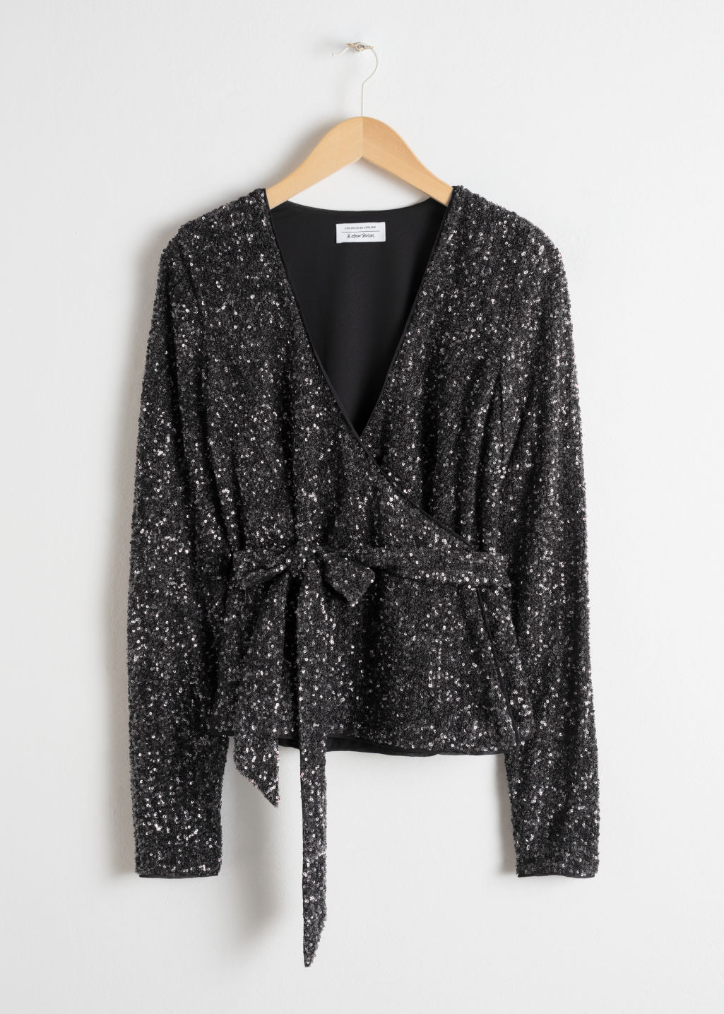 Front image of Stories sequin wrap top  in black