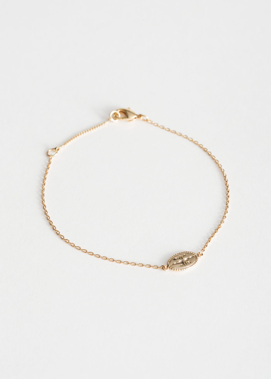 Front image of Stories engraved oval charm bracelet in gold