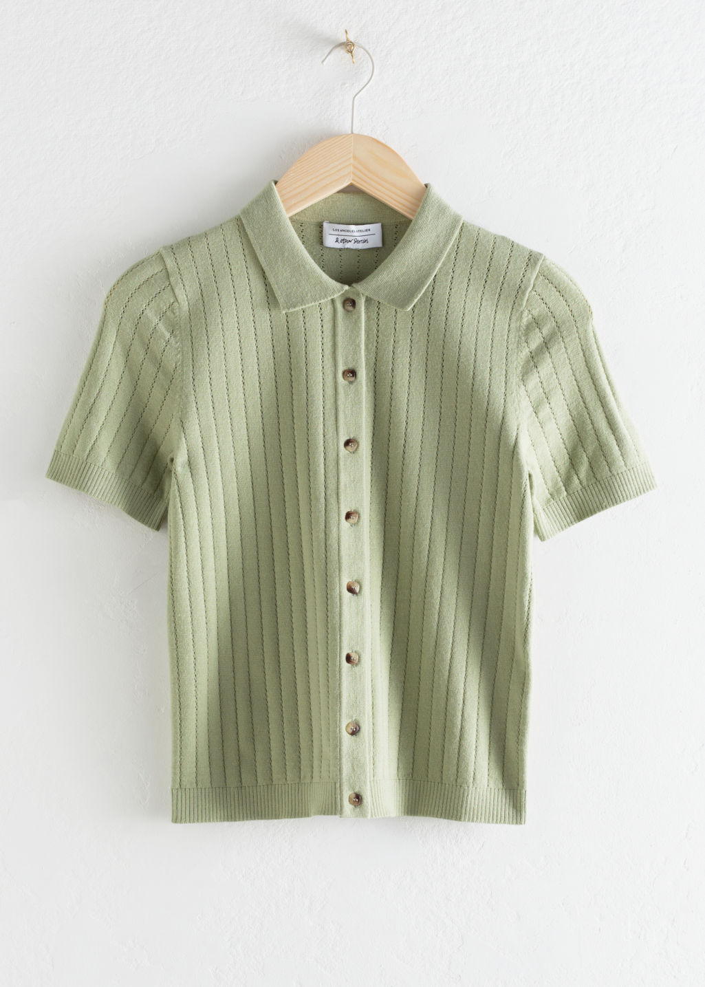 Front image of Stories eyelet knit polo top in green