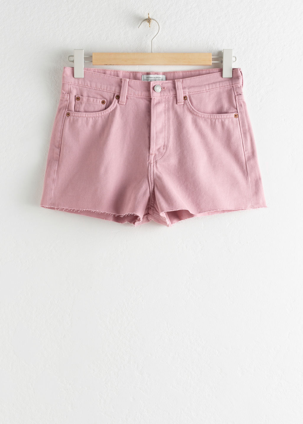 Front image of Stories raw hem denim shorts in pink