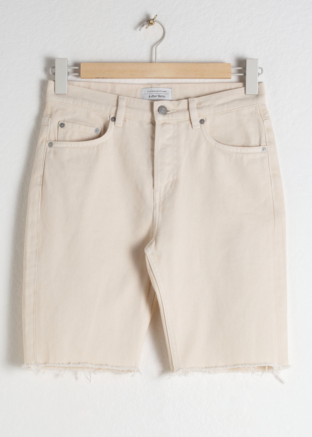 Front image of Stories raw edge denim bermuda shorts in white