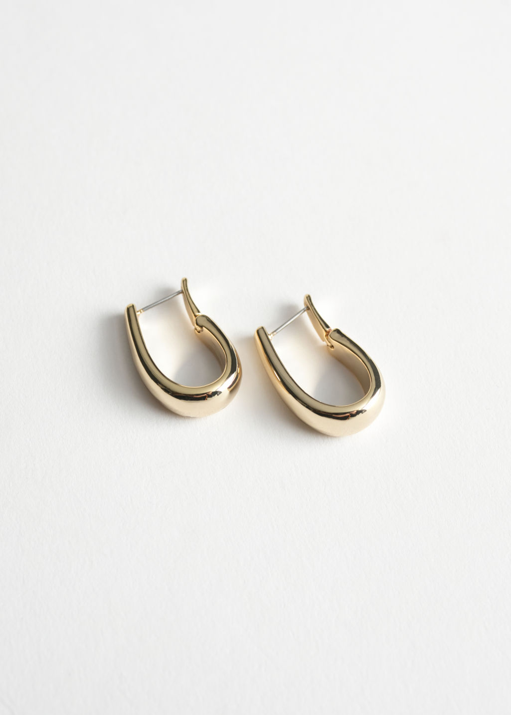 Front image of Stories horseshoe hoop earrings in gold
