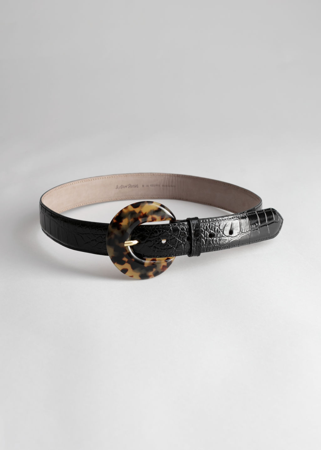 Front image of Stories tortoise circle buckle croc belt in black