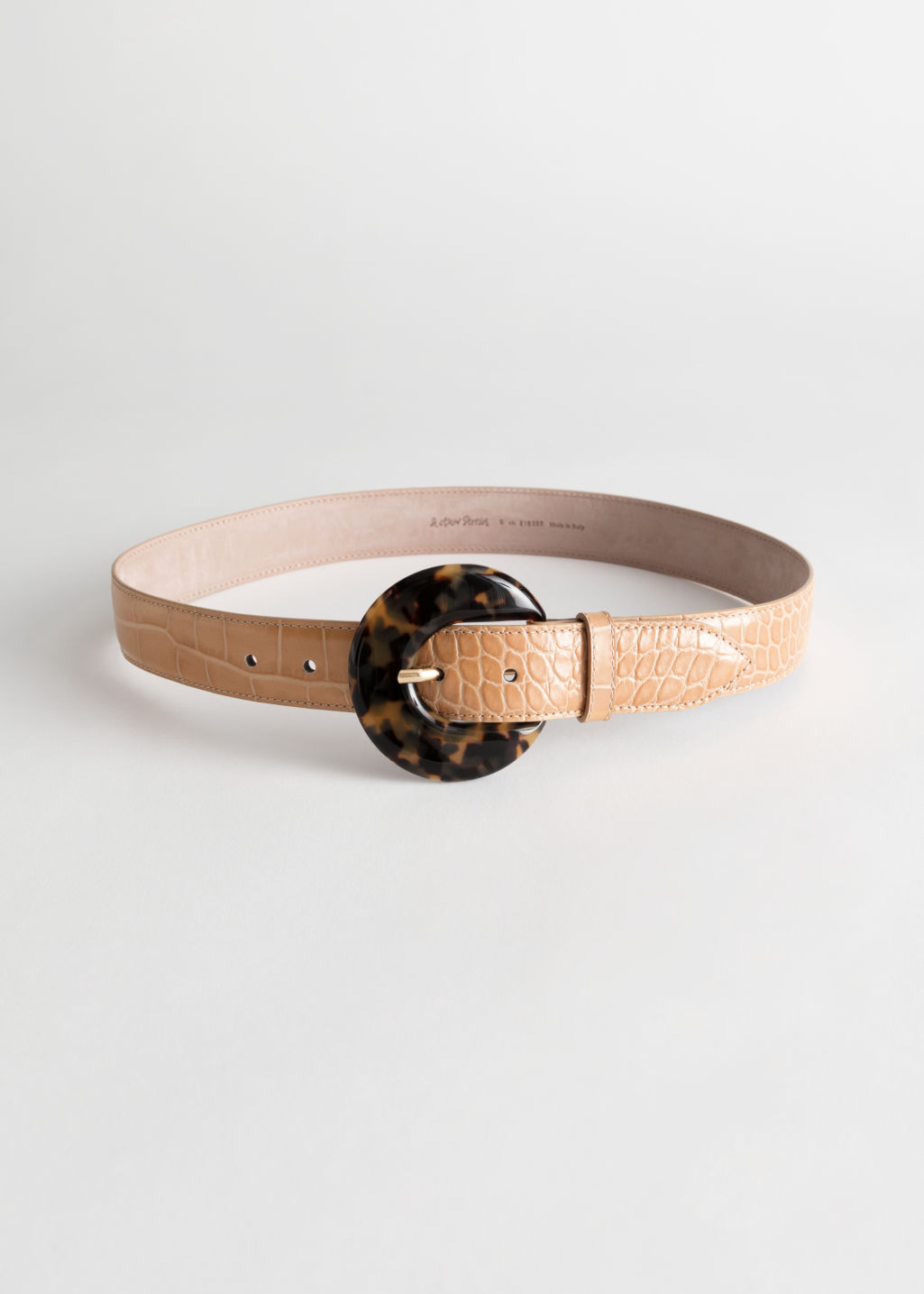 Front image of Stories tortoise circle buckle croc belt in beige