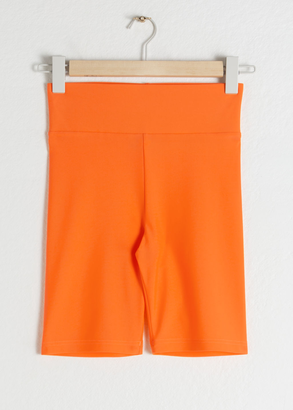 Front image of Stories fitted cycling shorts in orange