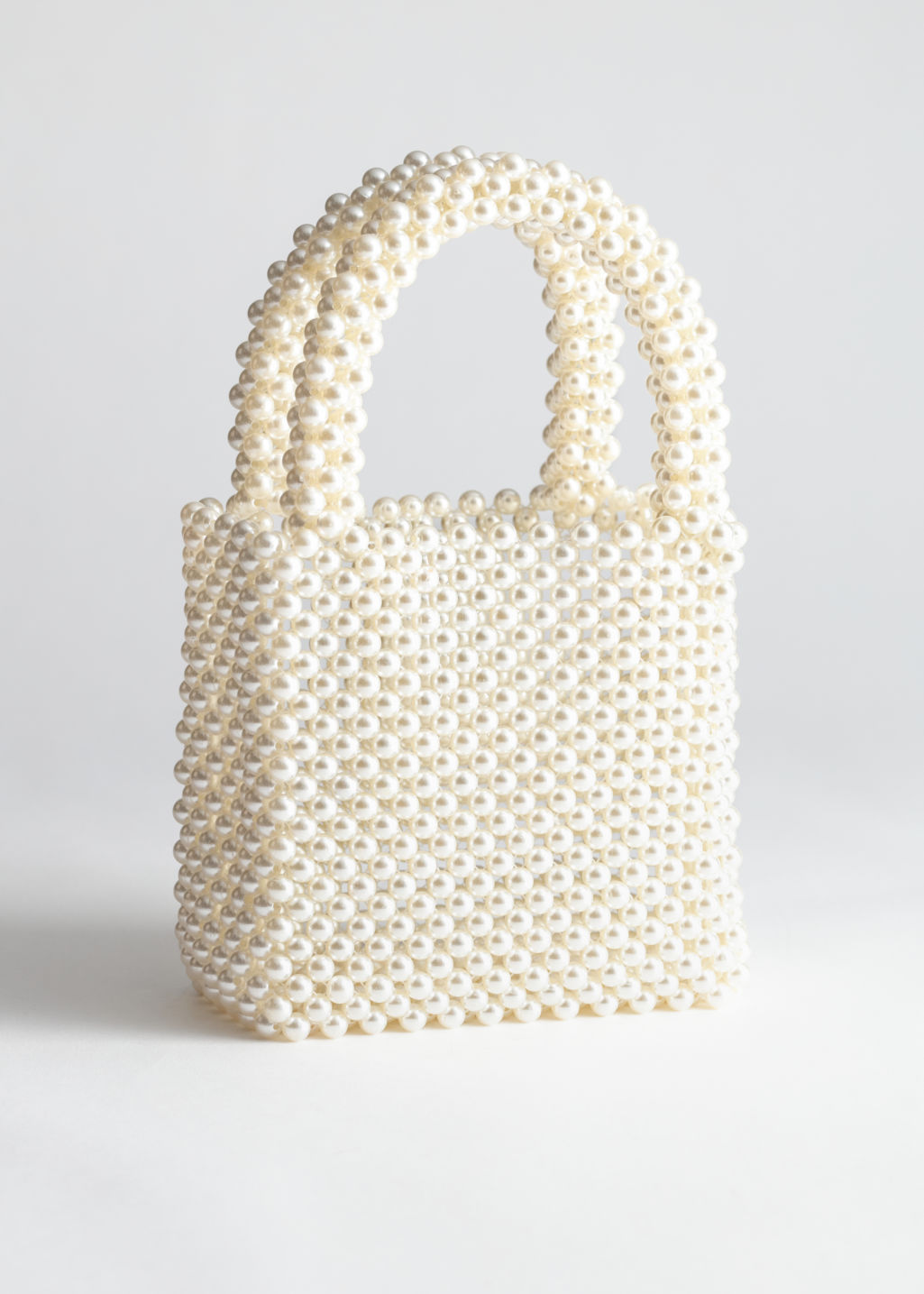 Front image of Stories pearlescent beaded clutch bag in white
