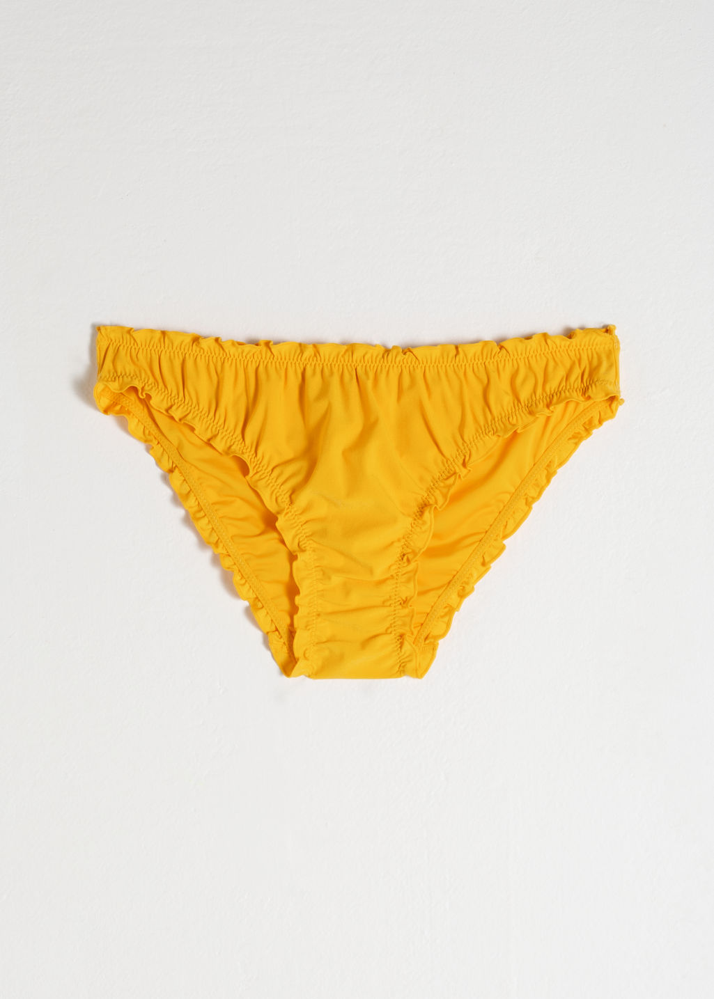 Front image of Stories ruffled bikini briefs in yellow