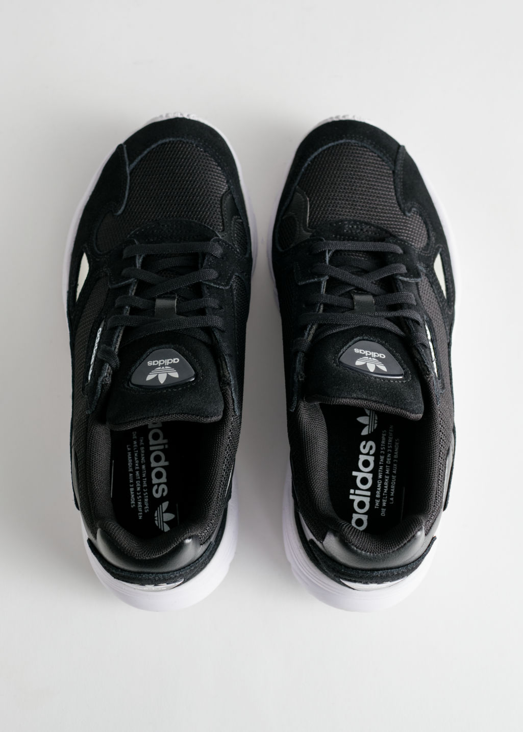 Back image of Stories adidas falcon in black