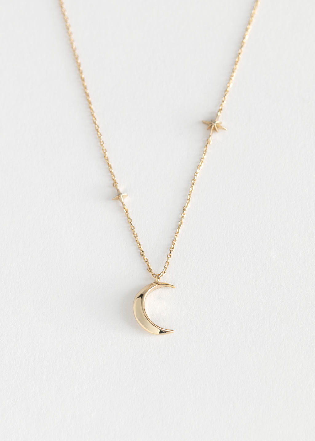 Front image of Stories crescent moon pendant necklace in gold